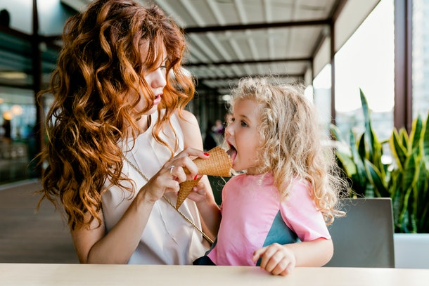 A young woman and her niece eat ice cream cones in a café on her niece's birthday.