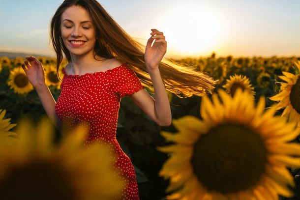 A woman spins around in a sunflower field with a red dress on.
