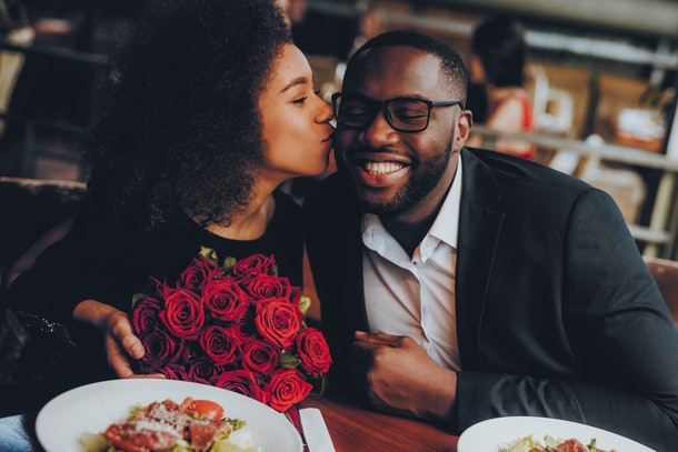 A woman holding a bouquet of red roses kisses her boyfriend on the cheek in a restaurant.