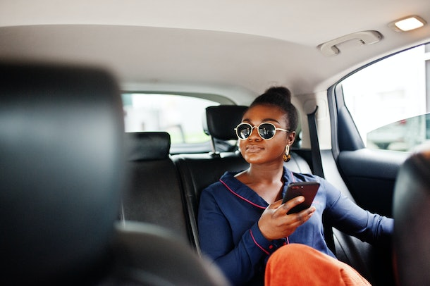 A chic woman sits in the back of a car and drives around a city with her phone in her hand.