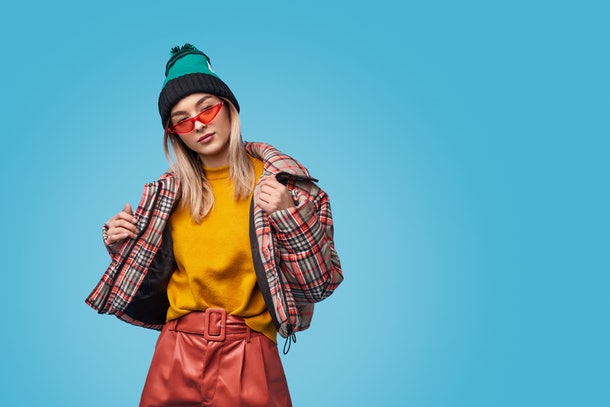 Weird young female in trendy outfit adjusting checkered jacket and looking at camera against blue background