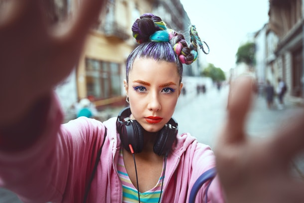 Cool funky young girl with headphones and crazy hair enjoy power of music taking selfie on street – hipster woman with trendy avant-garde look having fun - Music fan concept with playful carefree teen