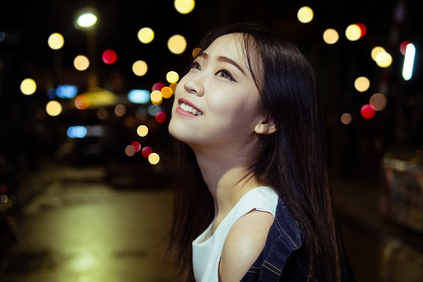 cute asian girl in the night light city with bokeh happiness emotions