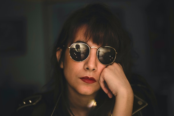 Rock woman resting on her hand with sunglasses and red lips