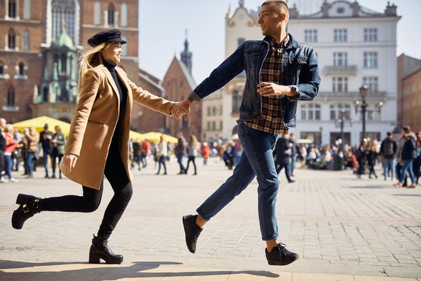 Lovely couple run on the street and smile