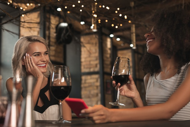 Amusing stories. Cheerful young women sitting at the bar counter, drinking wine and laughing heartily while sharing stories