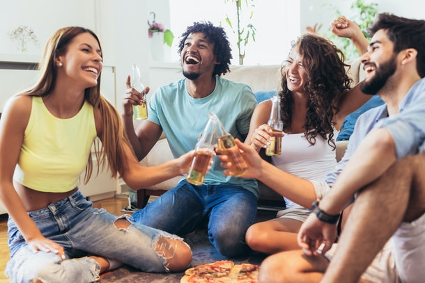 A group of friends clinks their beer bottles while laughing and enjoying pizza in a living room.