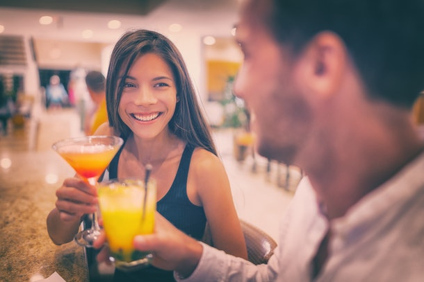 Bar drinking cocktails young couple in love dating talking with drinks at restaurant at night. People at restaurant with alcoholic cocktail beverage.