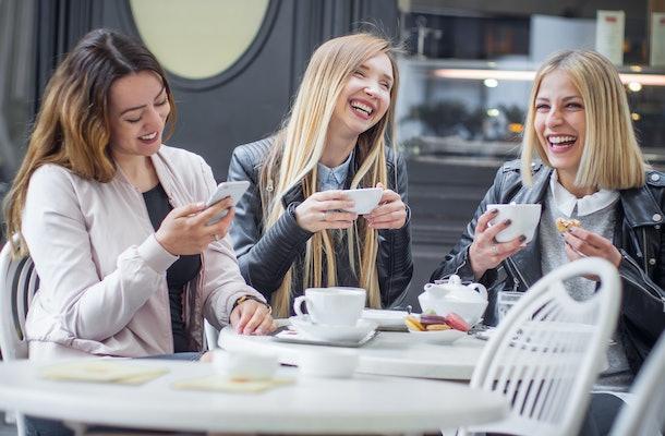 Three girls laugh while enjoying tea and macarons at an outdoor café.