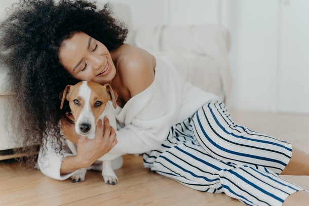 A woman dressed in a sweater and pajama pants cuddles with her dog at home.