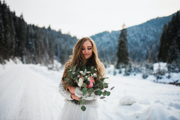 girl in a winter forest. bride with a bouquet. girl in winter in the mountains