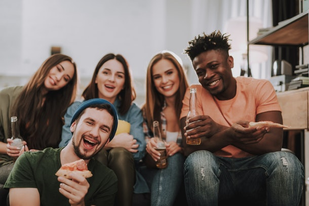 A group of friends eats pizza and drinks beer while watching the 2020 Super Bowl.