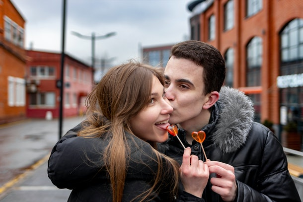 A happy couple holds heart-shaped lollipops in the street on a winter day.