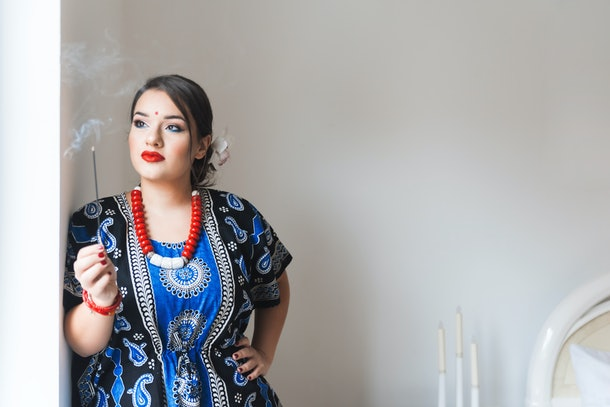 Beautiful mindful young indian woman  relaxing and enjoying incense stick in her home, Space for text