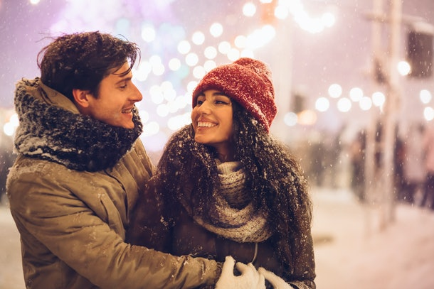 Happy Couple Hugging Celebrating New Year Night Outdoors Standing On A Street Decorated With Winter Lights.