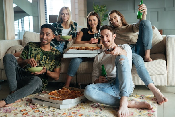 Five friends sit in a living room while watching TV and enjoying beer and pizza.