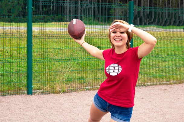 A blonde-haired woman in a red football shirt prepares to throw a football outside in the park.