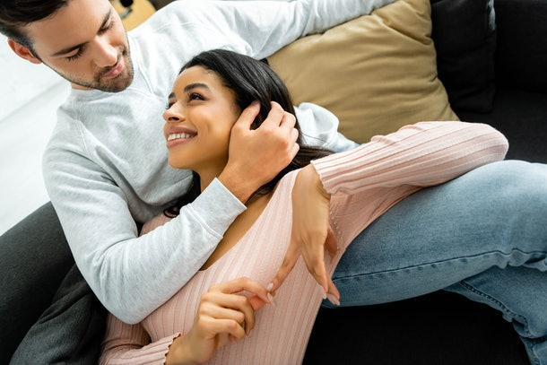 african american woman and handsome man smiling and hugging in apartment
