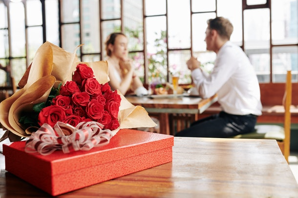 Horizontal shot of beautiful red roses and box of chocolate lying on cafe table, couple dating on background