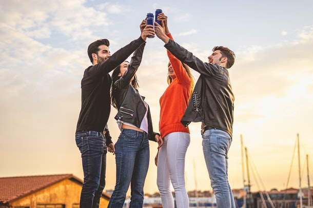 A group of friends toast their beer cans on a rooftop at sunset.