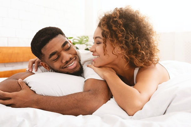 Loving black couple relaxing in bed at home, enjoying sweet good morning together