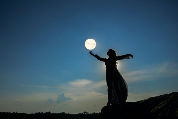 silhoutee of woman standing on top of mountain. female hold in hand full moon above forest trees. backlight and moon light. good vibes