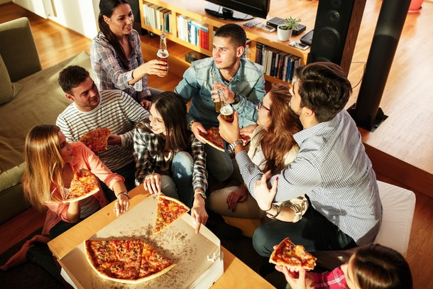 A group of friends enjoy pizza and beer at home.