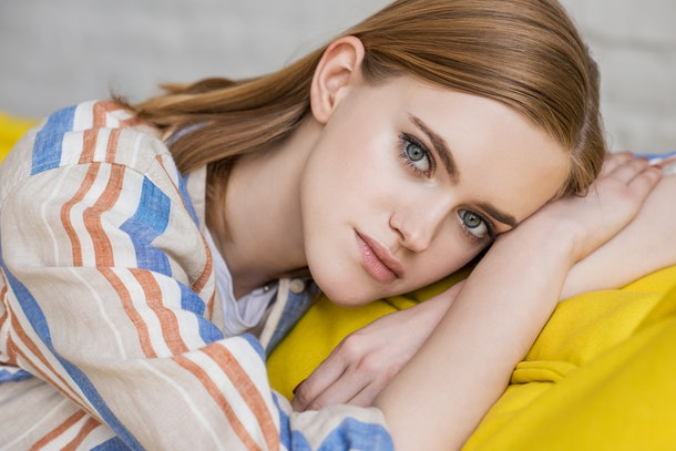 portrait of young attractive woman laying on couch