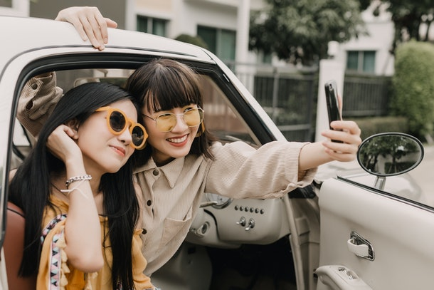 Two fashionable girls pose for a selfie on the seat of a car.