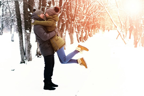 A happy couple embraces in the snow on a sunny day.