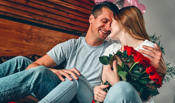 Celebrating Saint Valentine's Day. A man gave a woman a  red roses. A couple is sitting on the bed with heart-shaped confetti and hugging.