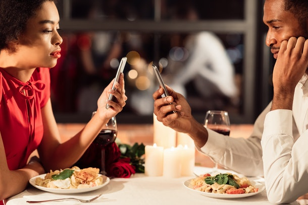 Boring Date. Bored African American Couple Using Mobile Phones During Romantic Dinner Ignoring Each Other Sitting In Restaurant. Selective Focus
