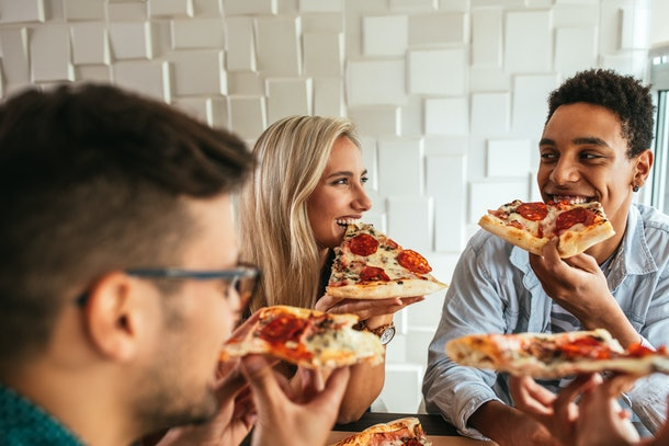A group of friends sits at a table and enjoys a pizza.
