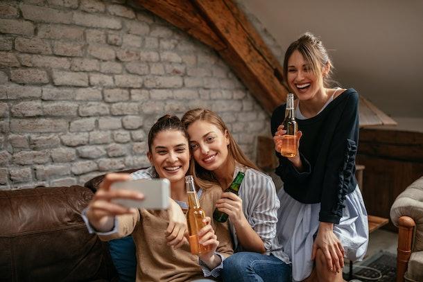 Three beautiful female friends taking a selfie in the apartment