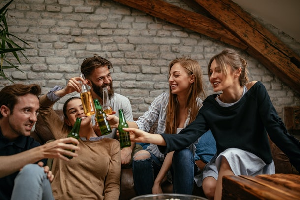 A group of friends clink their beer bottles while hanging out at home.