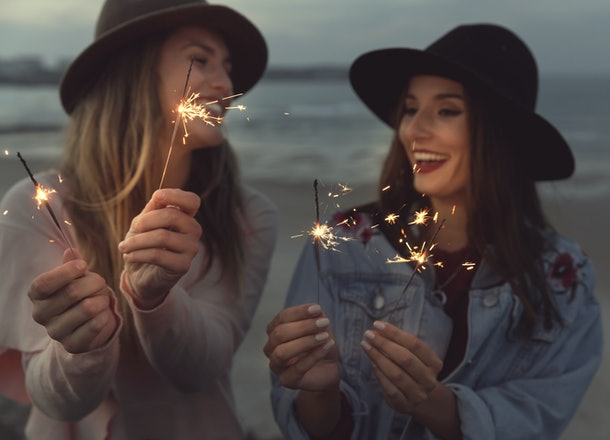 Two best friends in felt hats laugh and hold sparklers on the beach.