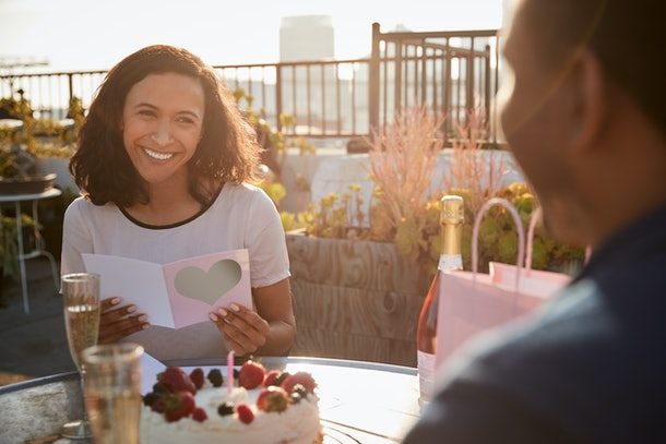 A brunette woman smiles at an outdoor restaurant while reading her birthday card.