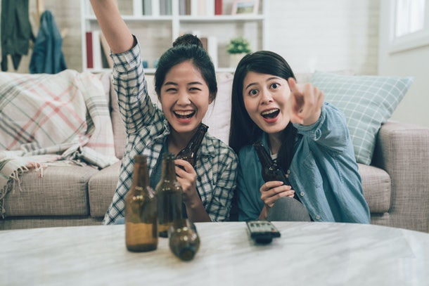 two excited asian women cheerful laughing celebrating victory win watching games on television tv pointing screen monitor. happy girls friends sitting on wooden floor with bottles of beer controller.