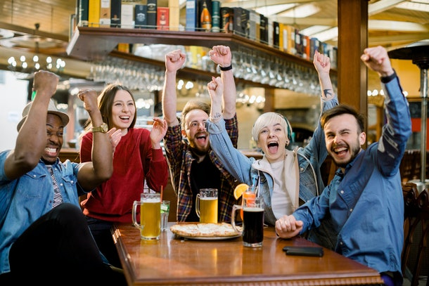 Excited diverse friends football fans celebrating victory goal score watching game online on tv in cafe supporting winning team drinking beer eating pizza together