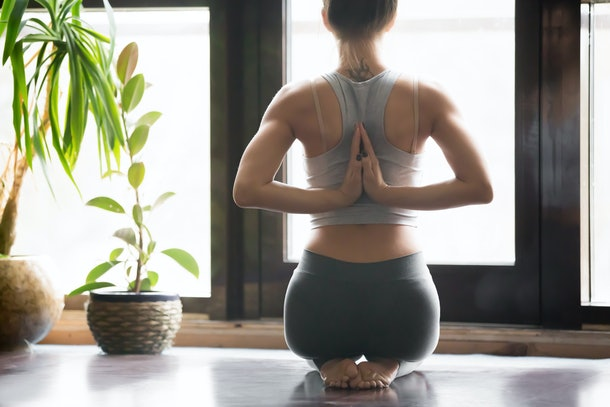 Young woman practicing yoga with namaste behind the back, sitting in seiza exercise, vajrasana pose, working out, wearing sportswear, grey pants, bra, indoor, home interior background, rear view