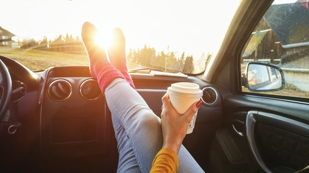 Young woman drinking coffee inside car in fall season - Girl relaxing and enjoying sunset traveling on europe mountains - Travel ,road trip and comfortable concept - Focus on paper hand