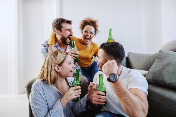 A group of friends enjoys beer and laughs in a bright family room.