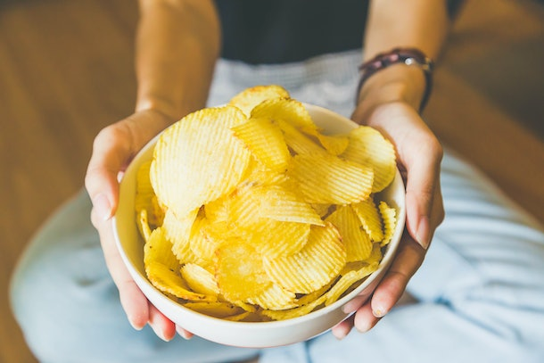 A woman sits on the floor and holds out a white bowl of potato chips.