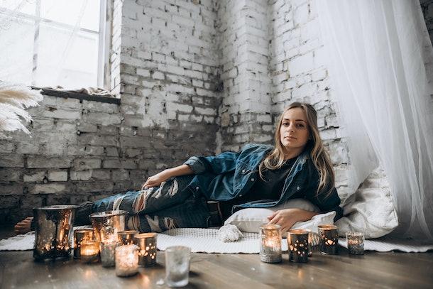 Amazing girl lies on the floor on the rug in her cozy bedroom