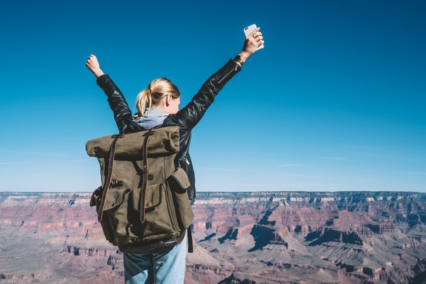 A girl stands with her phone and a backpack on the top of the Grand Canyon.