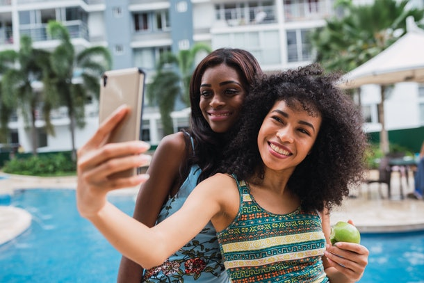 Two best friends in swimsuits smile and take a selfie by the pool.