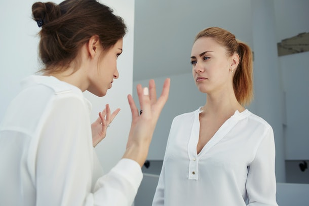 Half length portrait of a female managing director screaming on subordinate while standing in modern office interior, bad-tempered business executive yelling on her employee after unfortunate meeting