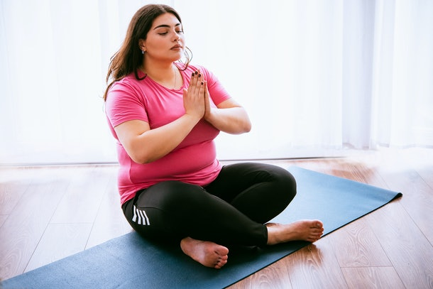 Beautiful plus size girl meditating indoors. Yoga and wellness concept
