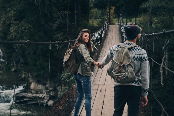 Making each other happy. Young smiling couple holding hands while walking on the suspension bridge