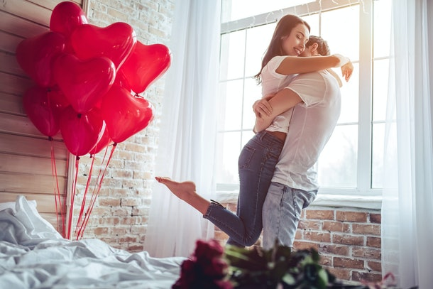 A happy couple embraces in a bedroom with heart-shaped balloons next to them on Valentine's Day.